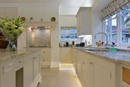 kitchen with white cupboards and marble surfaces