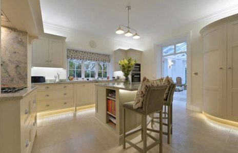 white modern fitted kitchen with marble worktops and under cabinet lighting
