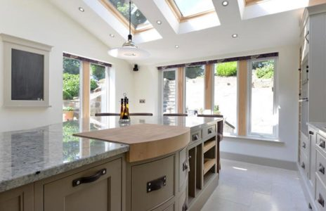 matte grey fitted kitchen storage units with overhead lighting and marble work surfaces