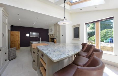 modern curved kitchen island with marble effect worktop and leather seats