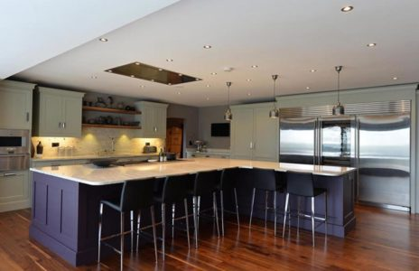 fitted kitchen island with black bar stool seating area and traditional wood worktop