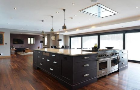 fitted kitchen island with black storage units and traditional wooden worktop