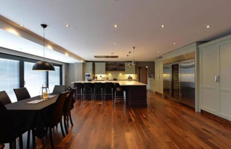 open plan fitted kitchen with black dining table, large silver fridge and white cabinets and worktops