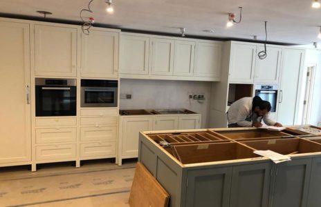 kitchen fitter measuring a white wood kitchen island
