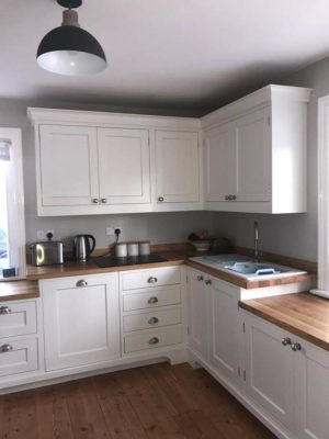 fitted kitchen with white cupboards and wood worktops