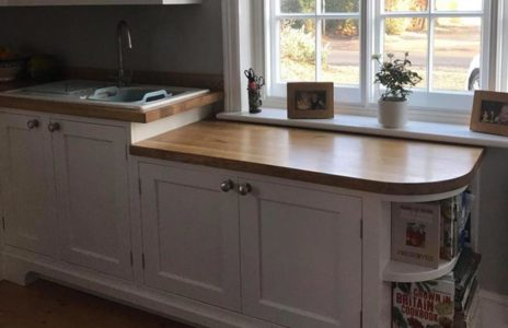 kitchen with wooden worktops and white cupboards