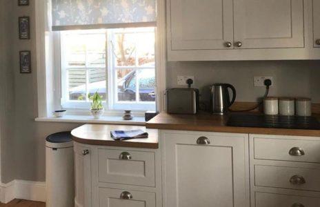 white wooden kitchen cabinets with wooden worktops