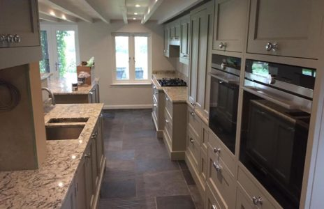 bespoke galley kitchen with dual oven and marble effect worktops