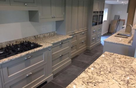 modern fitted kitchen with marble effect countertops and fitted appliances