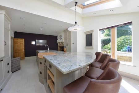 large kitchen with marble worktops and kitchen island