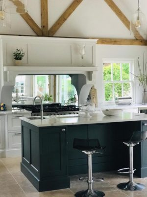 modern fitted kitchen with white worktops and green counters