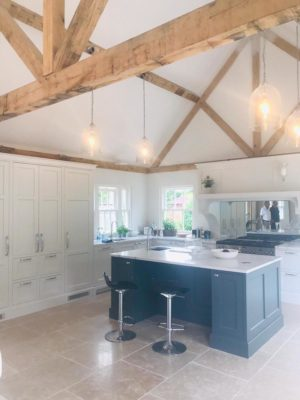 modern kitchen offset with traditional wooden beams and overhead lighting