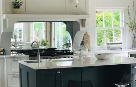 modern fitted kitchen with white countertops and decorative mirror above the stove