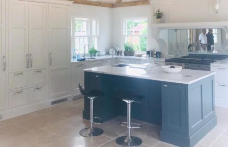 fitted kitchen with white countertop island and bar stool seats