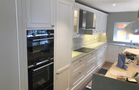 modern fitted kitchen with white worktops and duel oven