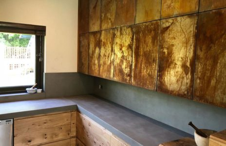 black fitted kitchen countertops with aged wood cabinets