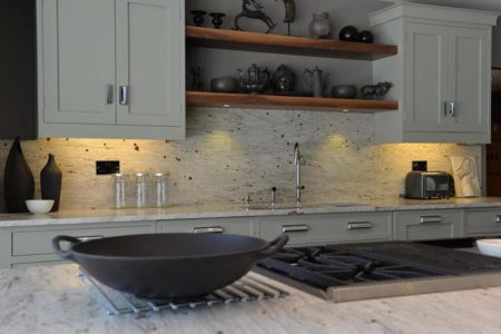 kitchen with marble worktops and white cupboards