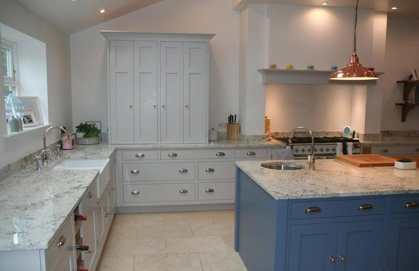 fitted kitchen with marble surfaces and blue cupboards