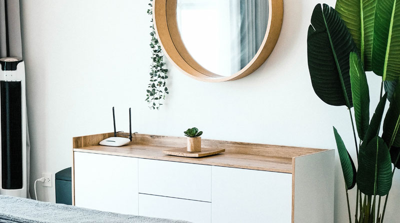 white sideboard with wooden round mirror