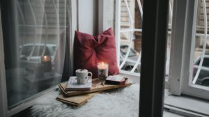 Quiet space near window with red cushion and candle
