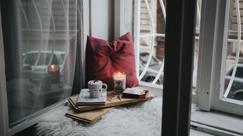 Quite space near window with red cushion and candle